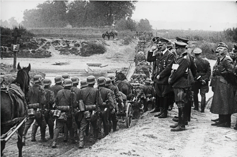 Hitler watching German soldiers march into Poland in September 1939.