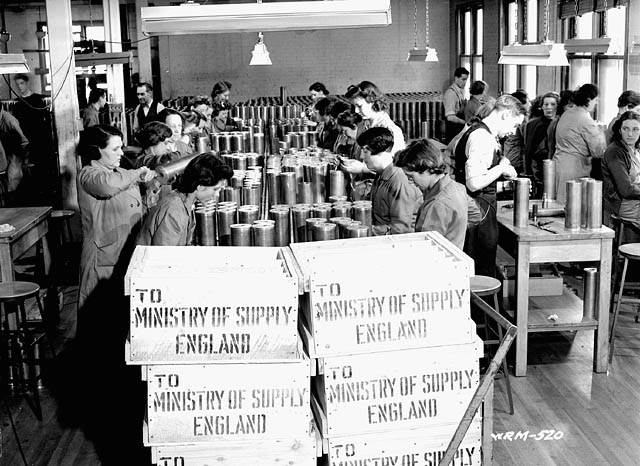 Men and women workers assemble 25-pounder field gun cases to be shipped to the Ministry of Supply in England at a munitions plant (prob. Robert Mitchell Co.)