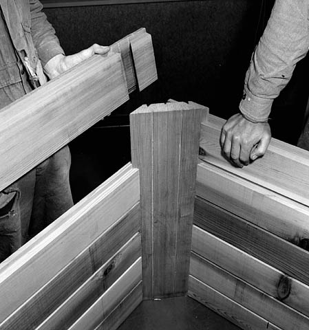 Workmen demonstrate the Loxtave (lock-stave) principle of prefabricated housing, using tongue and groove joints to hold walls tight